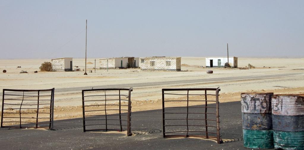 C'est un des nombreux check-points du désert Lybique: quelques barrières et tonneaux sur la route. Il est interdit de photographier les militaires.