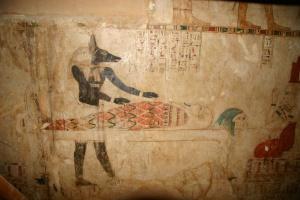 Le dieu Anubis, à tête de chacal, se tient près d'une momie. Il est le dieu de l'embaumement et le protecteur des nécropoles. Tombe de la XXVIe dynastie.