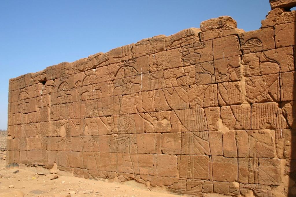 Moussawarat es-Soufra. Détail du relief du mur extérieur du temple d'Apédémak : le roi Arnékhamani et un prince, protégés par la déesse Isis, adorant le dieu lion Apédémak.