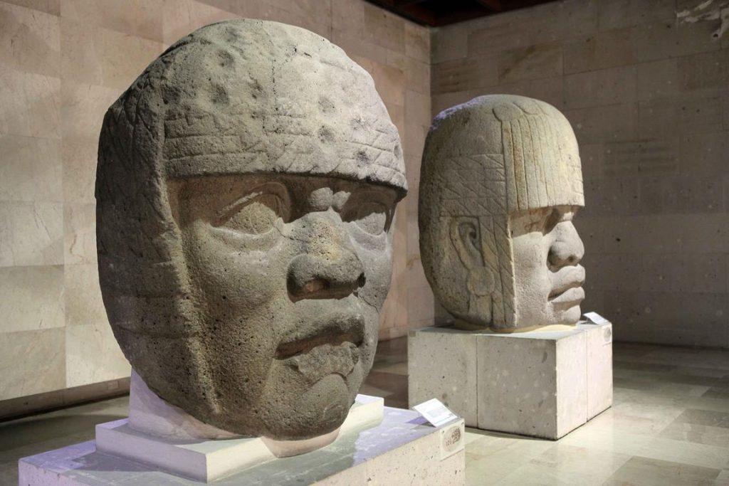 Têtes colossales n° 3 et 4. Ces têtes ont été trouvées sur le site de San Lorenzo Tenochtitlan, (État de Veracruz).La tête n° 3 est sculptée dans du basalte. Sur la coiffe formée de quatre cordes attachées, on peut observer la présence de trous correspondant à des mutilations intentionnelles contemporaines à l'époque préhispanique et Olmèque. Cette coiffe se termine par des couvre-joues à pli, probablement de tissu. La partie postérieure de la tête est plate. 1,78 × 1,63 m.