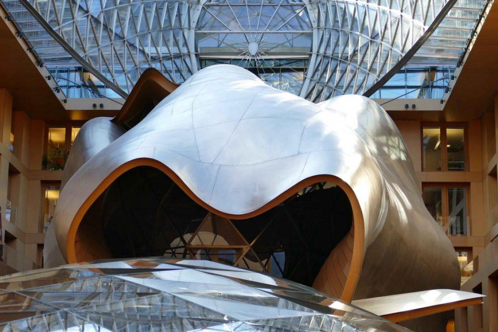 Dans l'atrium d'Axica, une sculpture spatiale monumentale de verre, de bois et de titane aux parois ondulantes, en forme de baleine, nous ouvre sa gueule : une prouesse de cet architecte visionnaire qui a également signé la fondation Louis Vuitton à Paris.