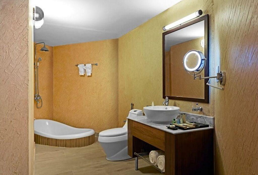Une belle salle de bain avec baignoire encastrée dans le sol, douche pluie et murs recouverts de chaux ocre complète la partie hébergement.