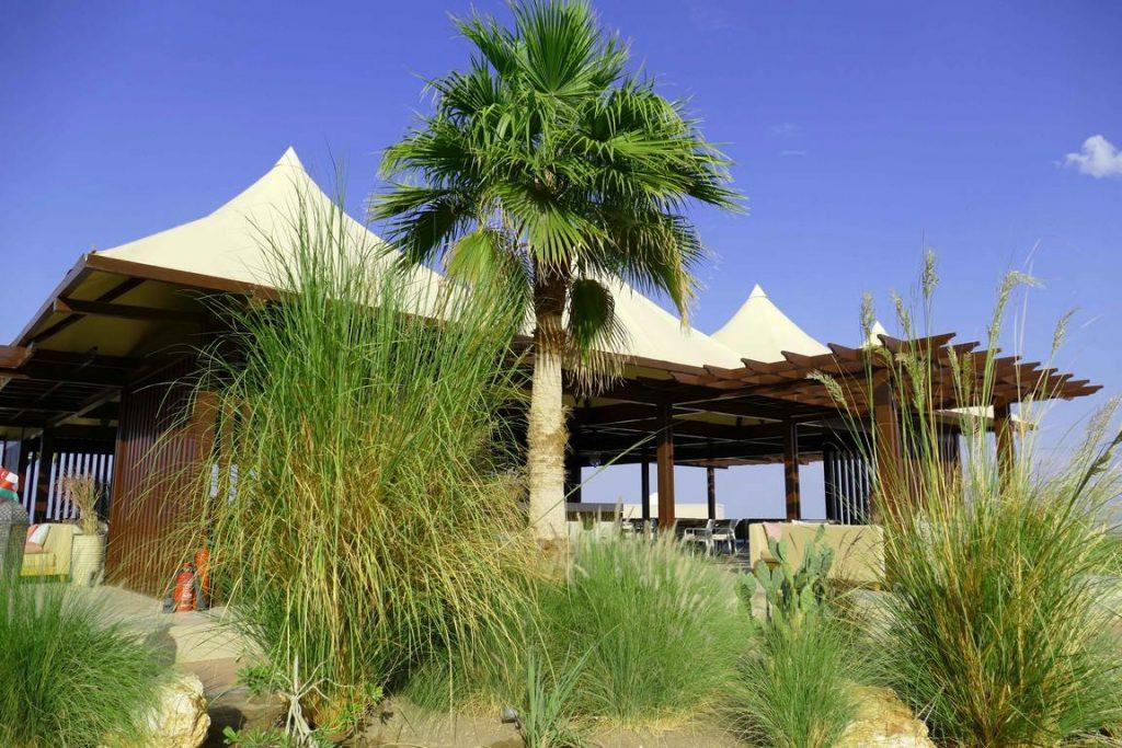 Centré autour d'un bar, le restaurant découpe des espaces intimes tout en étant ouvert sur la nature environnante.