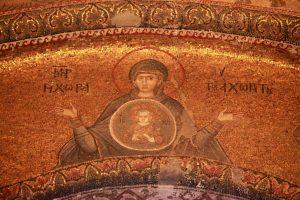 """Sur l'arc situé au-dessus du narthex extérieur, marie est représentée de face en prière. Jésus qui représente l'univers est en médaillon sur la poitrine de sa mère. De chaque côté, l'inscription """"Mère de Dieu, le lieu de celle que nul espace peut contenir."""""""