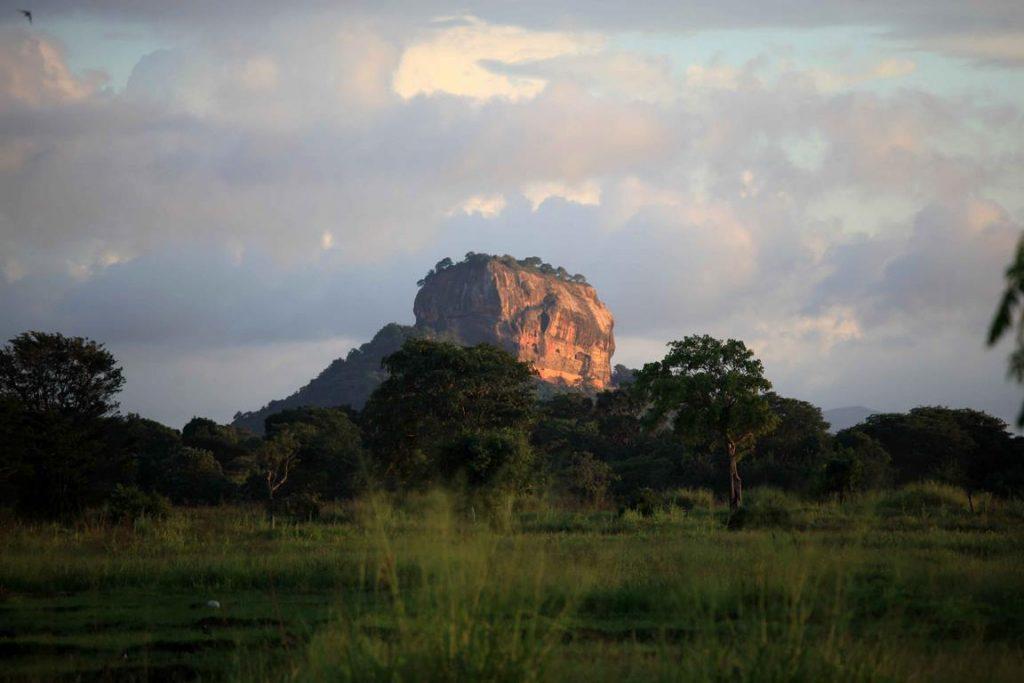 Sri Lanka. Sigiriya. Sur les pentes abruptes et au sommet d'un rocher de pierre rouge haut de 180 mètres, le « Rocher du Lion », qui domine la jungle de toutes parts, subsistent les ruines de la citadelle dont le roi parricide Kassyapa (477-495) fit sa capitale. Une série de galeries et d'escaliers qui débouchent dans la gueule d'un lion colossal construit en brique et en plâtre permettent d'accéder au site. Inscrit au patrimoine mondial par l'UNESCO, c'est le site archéologique le plus visité du Sri Lanka.