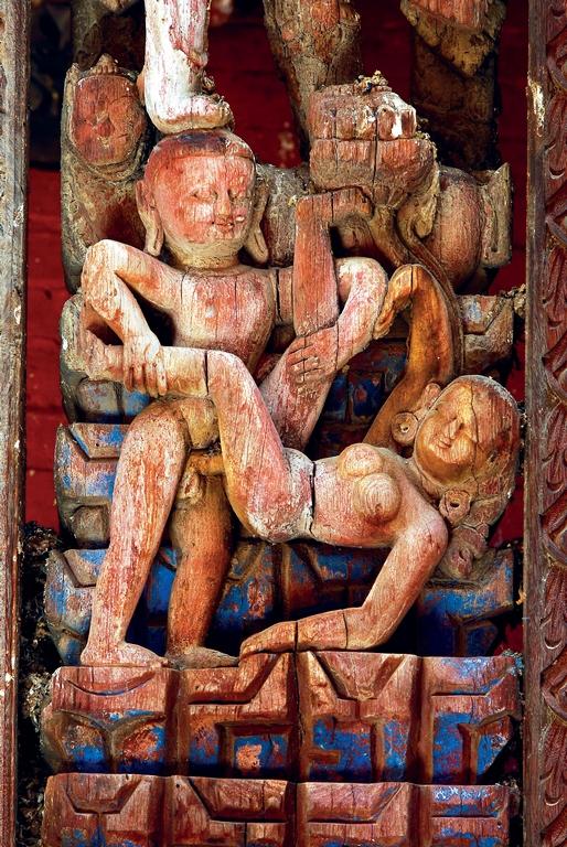 Bhaktapur. Temple de Pashupatinath. XVIIe siècle. Position du couple en maithuna décrite dans le Kama Sutra. Ce qui distingue la sexualité tantrique, ce ne sont pas les positions mais son rapport avec le divin. La femme, de son pieddroit soutient la fleur de lotus, elle-même reliée à la terre par sa tige, et sur laquelle la divinité repose son pied gauche. L'homme est en contact avec le monde divin par l'autre pied de la divinité qui les domine, posé sur sa tête. C'est l'union symbolique du ciel et de la terre mère qui nous est suggérée.