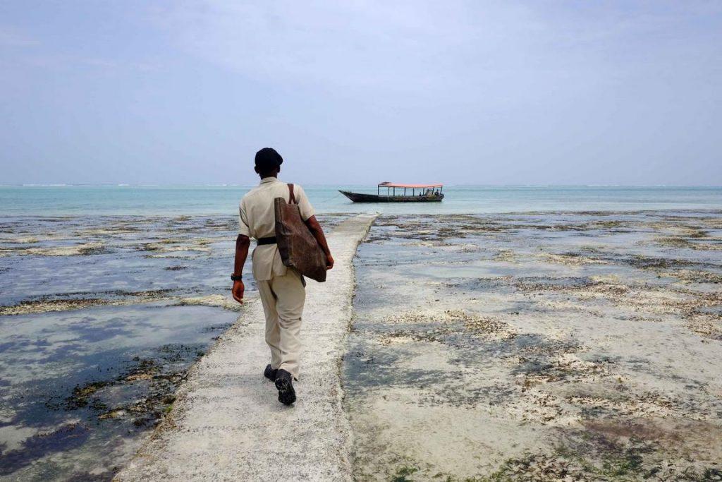 Zanzibar. Hôtel Zawadi. Le garde de l'hôtel accompagne les clients en bateau sur les récifs de coraux.