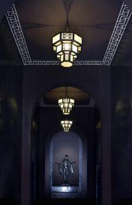 Marrakech. Villa Makassar. La porte sur rue, sculptée dans le cèdre et l'acajou, ouvre sur un long couloir de mystérieuse pénombre au bout duquel veille une statue de bronze.