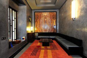 Marrakech. Villa Makassar. De part et d'autre de la cheminée, des fauteuils de Le Corbusier, éclairés d'appliques Jean Perzel regardent le personnage emblématique du salon : le Maharadja d'Indore, ici reproduit d'après un tableau de Bernard Boutet de Monvel.