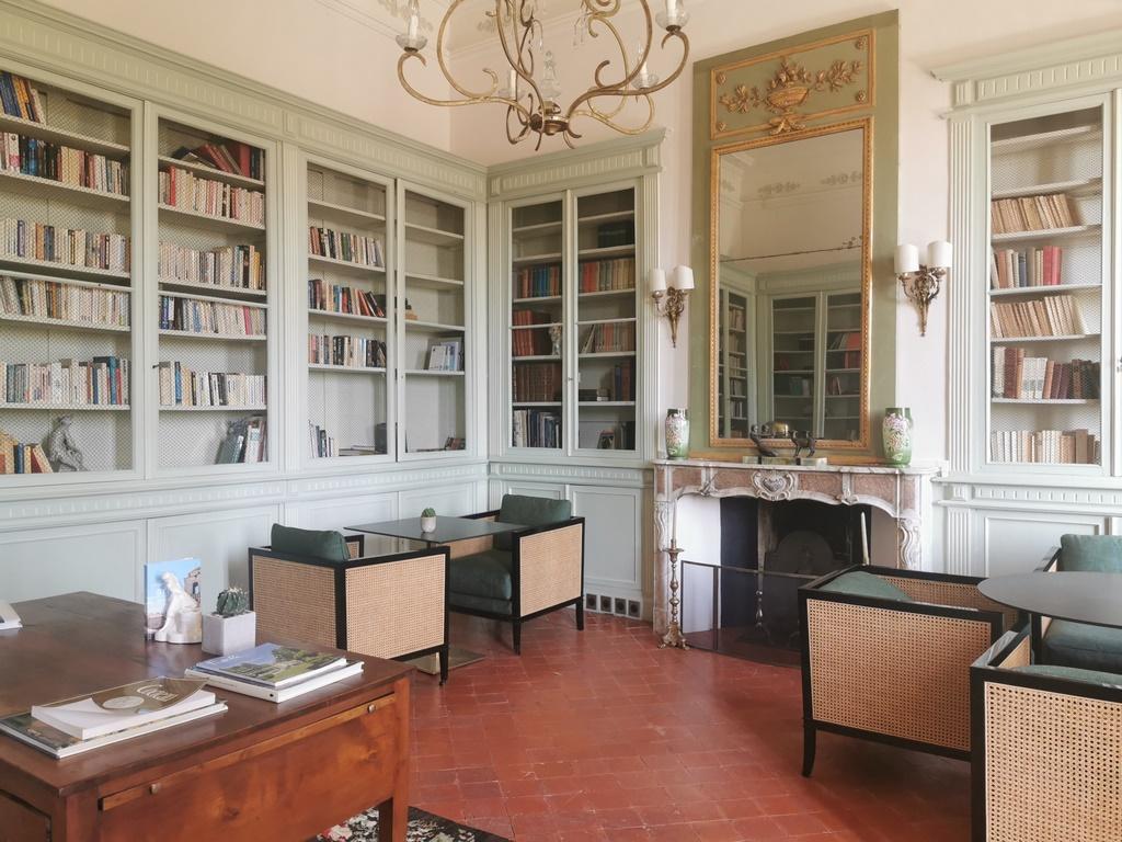 Carpentras. Château Martinay. Le salon de lecture a gardé ses boiseries et sa cheminée rocaille. que surmonte un miroir ancien.