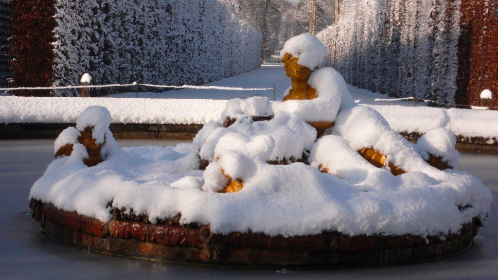 Château de Versailles. Bassin du Printemps. Sur une île ornée de guirlandes de neige à défaut des fleurs cachées, Flore apparaît sous sa toque blanche entourée d'Enfants ailés. Elle regarde dans la direction du lever du soleil au jour de l'équinoxe de printemps.
