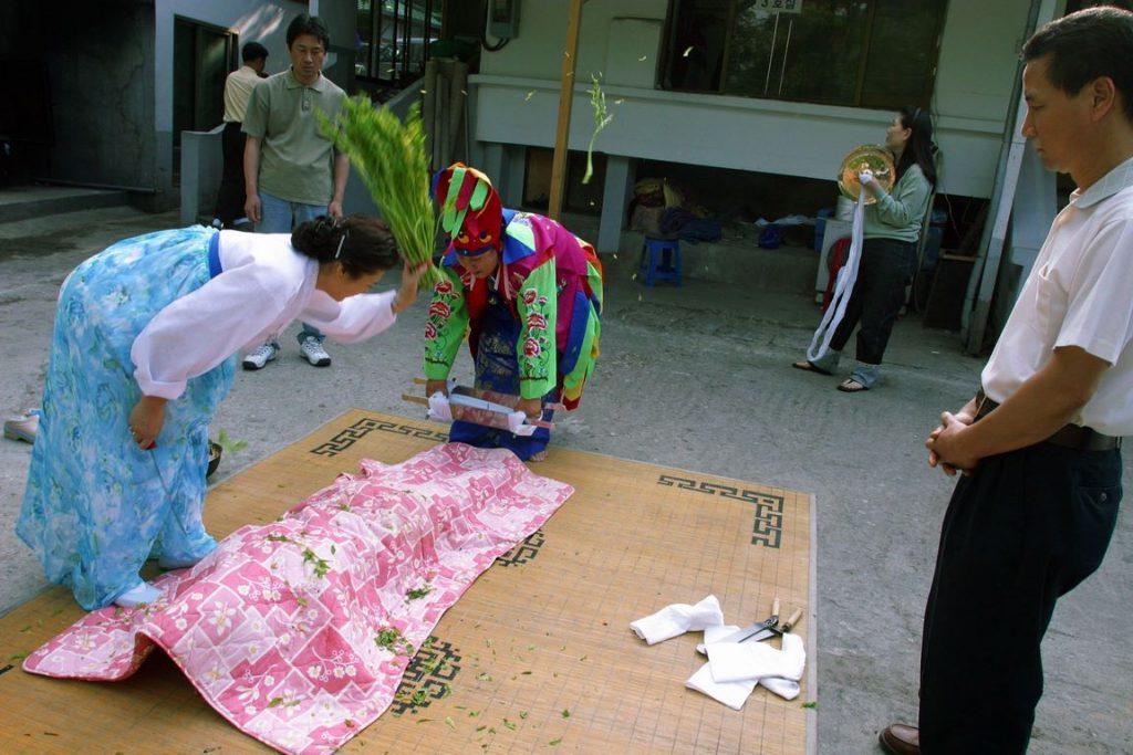 Corée du Sud. Rituel chaanique. L'assistante de la mudang se prépare à purifier une malade avec des tiges de riz.