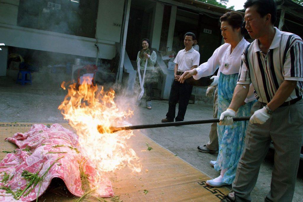 Corée du Sud. Rituel chamanique ou kut. Purification de la malade par le feu réalisée par l'assistante de la mudang.