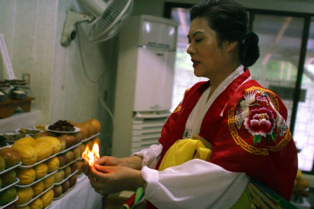 Corée du Sud. Rituel chamanique ou kut. La mudang purifie les tables-autels qui délimitent une aire sacrée.