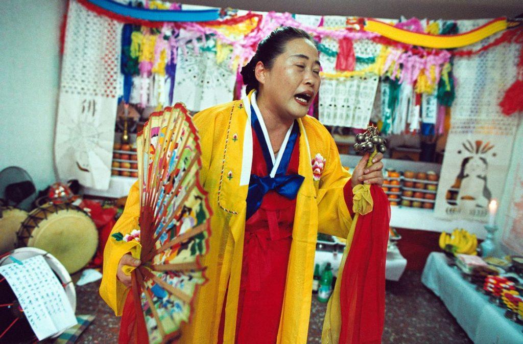 Corée du Sud. Rituel chamanique. La mudang aces ses grelots et son éventail convoque les esprits pour aider la personne pour laquelle le kut est organisé.