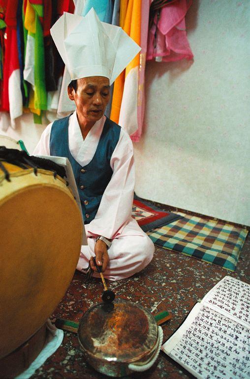 Corée du Sud. Rituel chamanique ou kut. Alors que les assistants se frottent la paume des mains en signe de recueillement, les musiciens commencent à frapper tambours et cymbales sur un rythme vif et insistant.