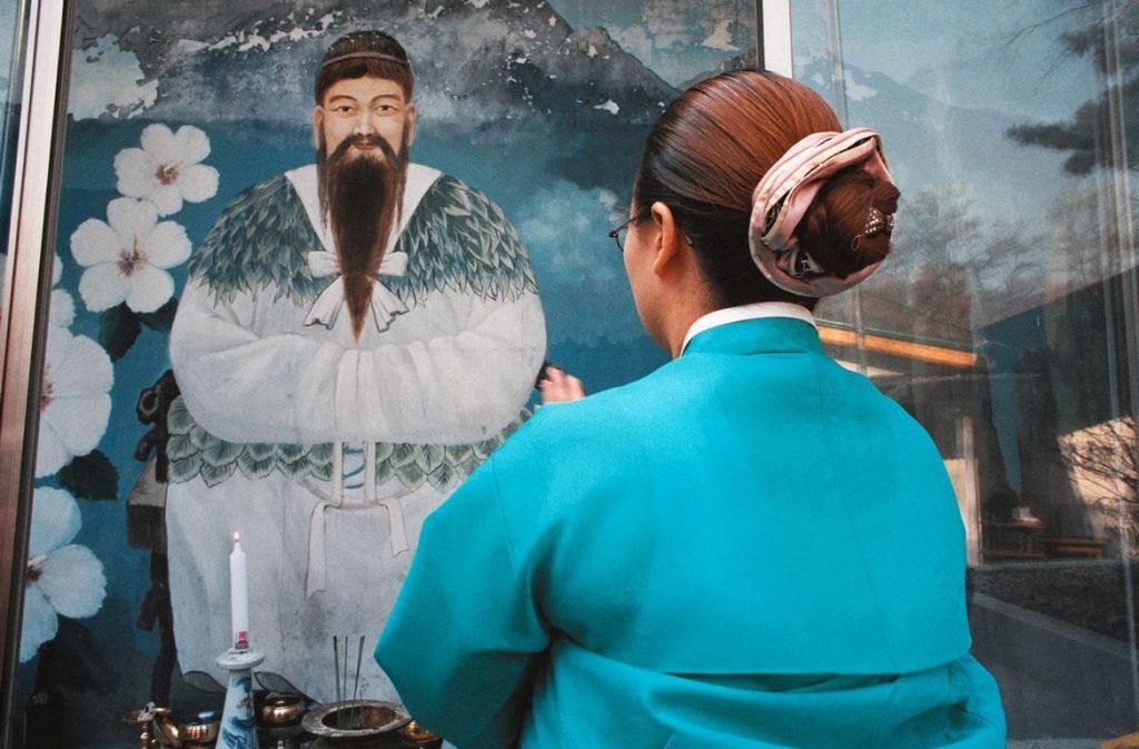 Corée du Sud. Rituel chamanique. Le kut débute par une offrande de prières aux déités et esprits du panthéon chamanique. Elle s'incline devant une effigie de Dangun, fondateur légendaire de Ko-Chosŏn, le premier royaume coréen.