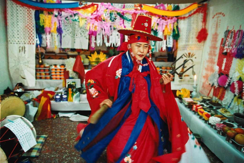 Corée du Sud. Rituel chamanique ou kut. La mudang dans dans l'espace rituel constitué des tables avec les offrandes aux divinités.