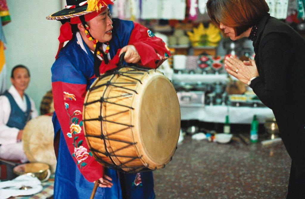 Corée du Sud. Rituel chamanique ou kut. La mudang appelle les esprits bienveillants avec son tambour.