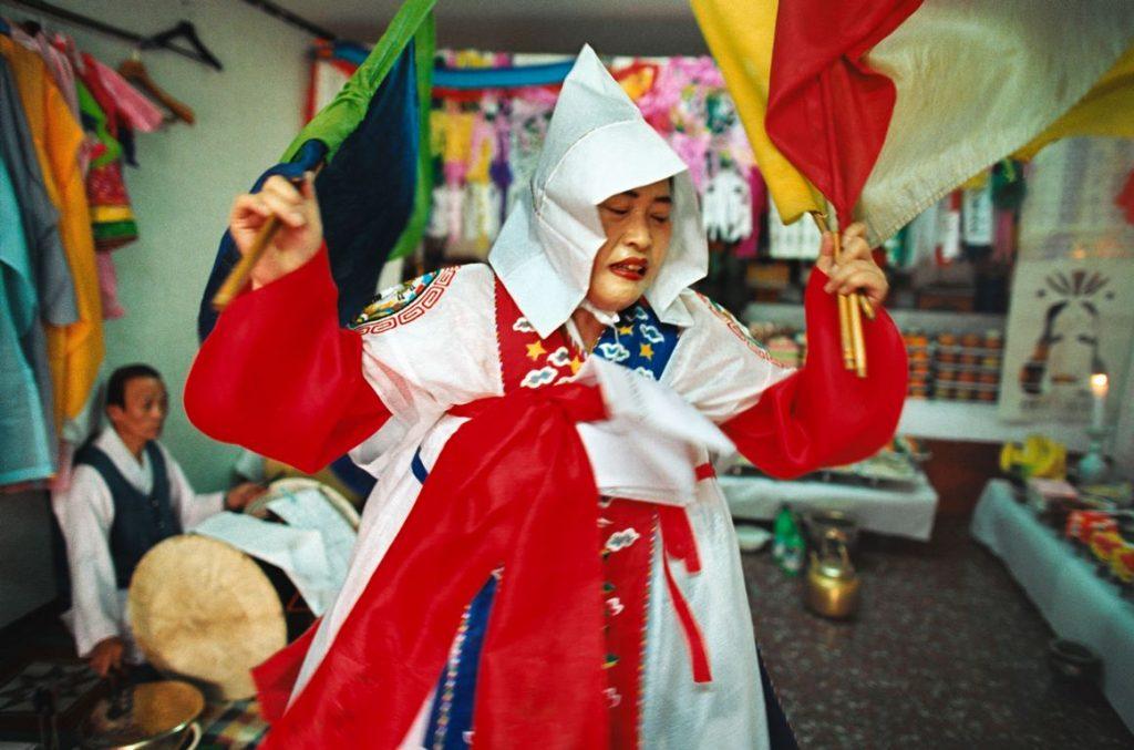 Corée du Sud. Rituel chamanique ou kut. Tour à tour, la chamane brandit des sabres ou des drapeaux, agite un bouquet de tiges de riz, sert de l'alcool, lance du riz pour apporter le bonheur.
